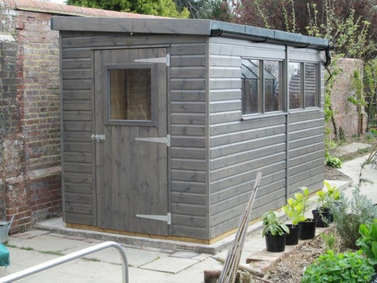 A small garden shed with a pent sloping roof and single door with a window in it. There are windows and black guttering along the side of shed and shiplap cladding coated in Sikkens preservative stain.
