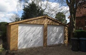 A large timber double garage with white up and over doors and shiplap cladding. The cladding is stained with a light oak lacquer. The garage has an apex roof.
