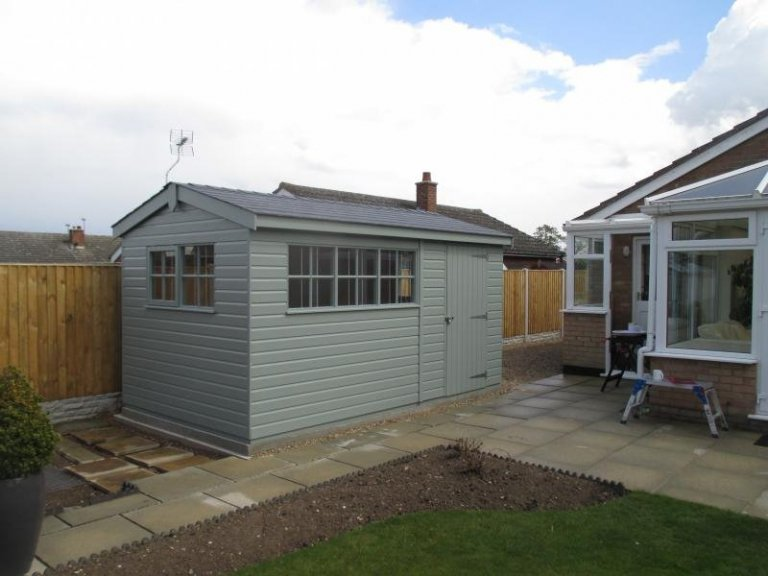 An attractive superior shed with a wide side and narrow gable. It has an apex roof covered with grey slate composite tiles and georgian windows.
