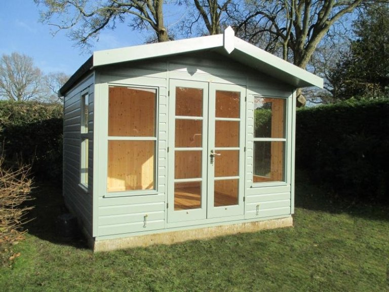 A small summerhouse with chalet-style look and double doors, opening window and apex roof with overhang. It is clad with shiplap timber and painted in the exterior shade of Lizard.