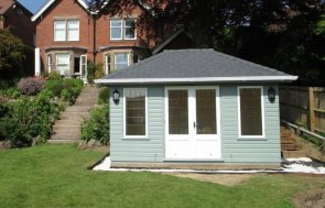 A shiplap cladded Garden room with leaded windows and a hipped roof covered with grey slate composite tiles