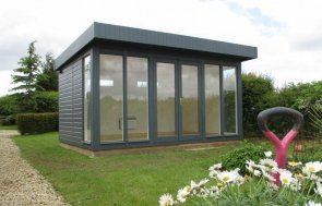 A modern and sleek salthouse garden studio with shiplap cladding and floor-to-ceiling windows