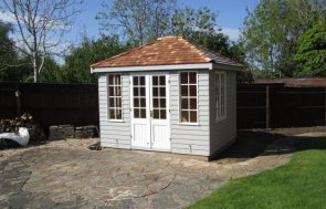 Cley Summerhouse with two tone paint in pebble and ivory with georgian windows. The hipped roof is covered with cedar shingles