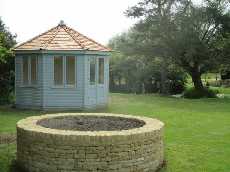An octagonal summerhouse with shiplap cladding and cedar shingle roof. There are several opening window sets that feature leaded glass.