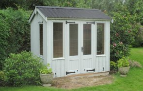a small summerhouse with traditional vertical cladding painted in the national trust shade of disraeli green with leaded windows and cast iron door furniture.