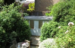 A garden studio in a bushy garden pictured behind the shrubbery. It has an apex roof and shiplap cladding.