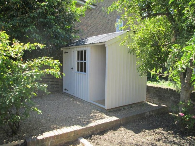 An attractive garden shed with vertical cladding and corrugated roof. From National Trust Garden Sheds range. Painted in Dome Ochre and has georgian windows.