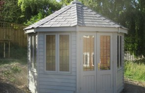 An octagonal summerhouse clad with rustic weatherboard and slate comp0ite roof tiles, it has leaded windows.