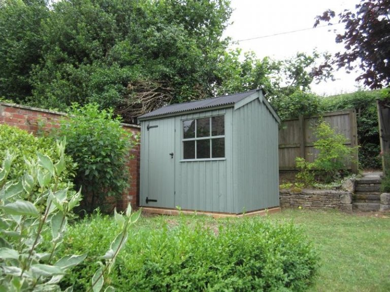 A small apex National Trust shed with vertical timber cladding and a corrugated roof, painted in Terrace Green.
