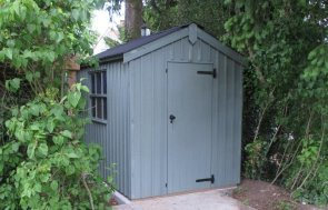 A charming garden shed with an apex roof covered in corrugated material and vertical rustic cut cladding. It is from the National Trust collection and is painted in the National Trust shade of Painter's Grey