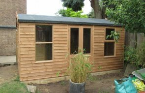 An attractive timber summerhouse with apex roof covered in felt. It has weatherboard cladding painted in light oak preservative and double half glazed doors
