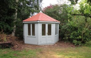 A distinctive, octagonal shaped summerhouse clad with smooth shiplap and a roof covered in red slate composite tiles