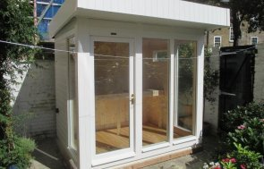 A small modern garden studio with a pent roof and smooth shiplap cladding painted in cream. It is lined internally with natural pine lining and has floor-to-ceiling windows for plenty of natural light.