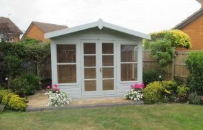 An attractive summerhouse with apex roof and chalet style double doors with windows and roof overhang. It has a lacquered floor inside and opening windows.