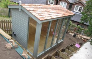A Burnham Studio in an elevated position in a banked garden. Steps leading up to it and birds eye view of cedar shingle roof. It has floor to ceiling windows and view of terraced houses in background. Garden studio with external electrical socket.
