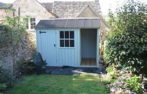 A small apex National Trust Shed with vertical timber cladding and a corrugated roof, painted in Disraeli Green.