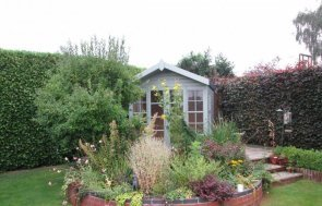 a blakeney summerhouse in customer garden. chalet style summerhouse with roof covered in heavy-duty felt and the option to add electrics and insulation inside the summerhouse.