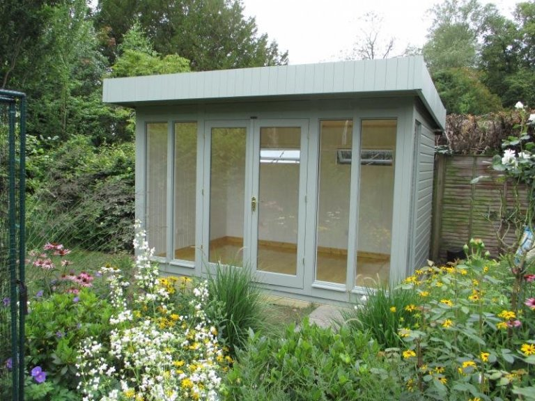 A medium sized contemporary modern stylish garden studio with electrics and painted interior. It has floor-to-ceiling windows and  opening fanlight windows.