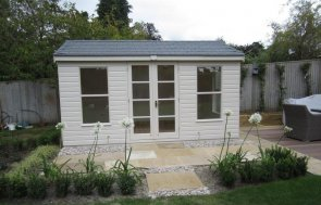 A cream summerhouse with slate tile covered roof and shiplap cladding. Summerhouse with double doors and opening windows with internal painting insulation and electrics.