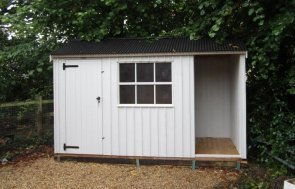 An attractive National Trust shed with built-in log store and rustic cladding painted in earls grey.