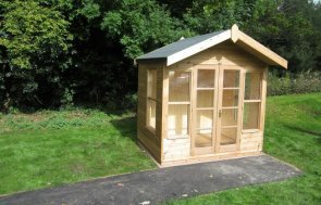 A small chalet-style summerhouse with felt-covered apex roof. Timber summerhouse in beach hut style. Double doors and several windows with a natural interior of pine. The roof has a slight overhang for shelter and shade.