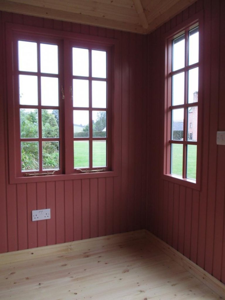 The interior of a cley summerhouse with georgian windows and insulation. The interior has been painted with a colour matched paint at the request of a customer.