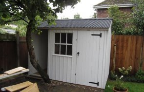 National Trust garden shed with built in log store. Apex roof covered in corrugated material and vertically-sawn rustic cut cladding for rustic garden shed look.