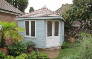 Traditional corner summerhouse with insulation and electrics. The summerhouse has leaded windows and a hipped roof covered in cedar shingles. It is painted in two-tone paint with colours from our paint range.