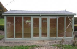 A bespoke garden studio with floor-to-ceiling windows and an apex roof covered with grey slate composite tiles. Internally it is lined with insulation.