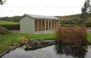 Garden Studio with apex roof and floor-to-ceiling windows beside large garden pond. It is an insulated garden studio with electrics and shiplap cladding on the exterior.