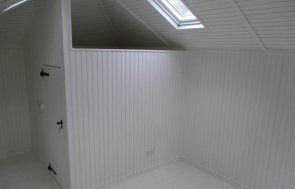 An interior image of the garden room with partitioned loft space and everything painted in white. There are velux windows visible and cast iron door furniture on a joinery door leading into partitioned area.