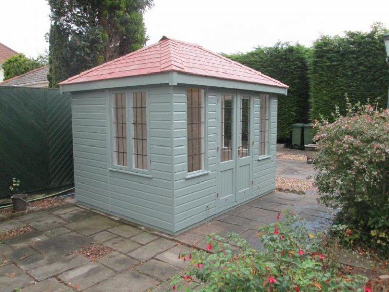 small summerhouse with hipped roof and insulation. Slate roof and leaded windows with double doors and shiplap cladding.