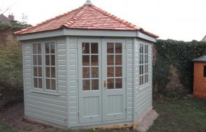 A large timber summerhouse with insulation and linings. A garden summerhouse with electrics and cedar shingle roof.