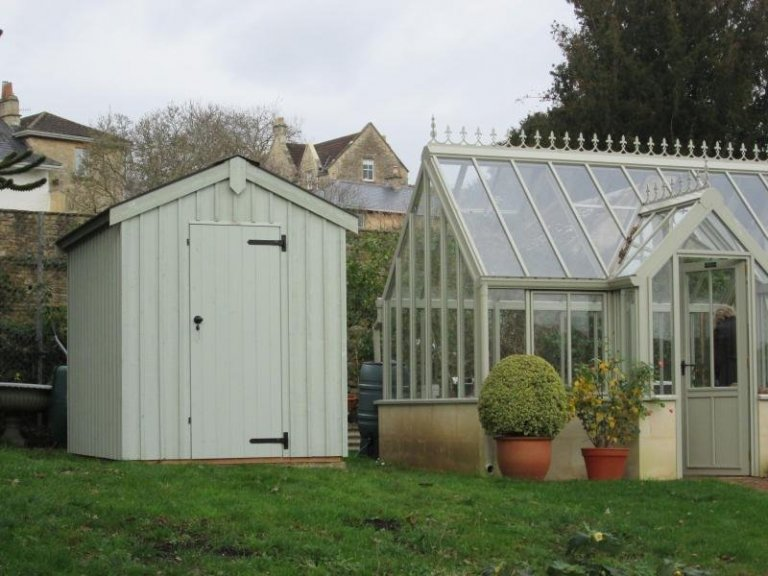 An apex national trust garden shed with traditional features such as corrugated roof and vertical rustic timber cladding. A timber garden shed with cast iron door furniture painted in the national trust shade of disraeli green.
