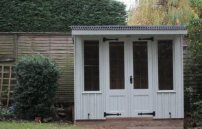 A traditional cream summerhouse from the national trust range of sheds and summerhouses. It has double doors and leaded windows and distinctive vertical cladding of rustic timber.