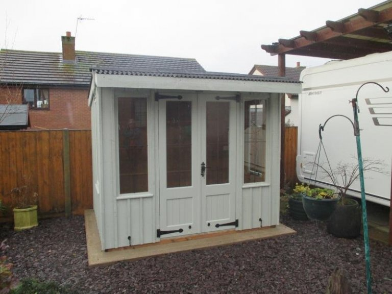 A traditional national trust summerhouse with double doors and leaded windows. It has a pent roof covered with corrugated material and cast iron door furniture.
