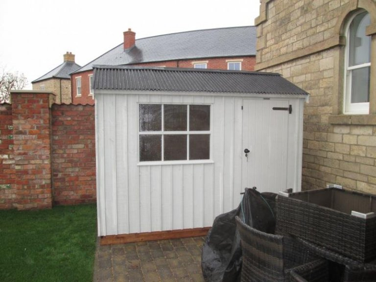 A small apex National Trust shed with vertical timber cladding and a corrugated roof, painted in Dome Ochre.