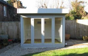 A modern garden studio with a pent roof and smooth shiplap cladding painted in the shade of Pebble. It has floor-to-ceiling windows for plenty of natural light inside the building. The garden studio also has electrics and heating installed.