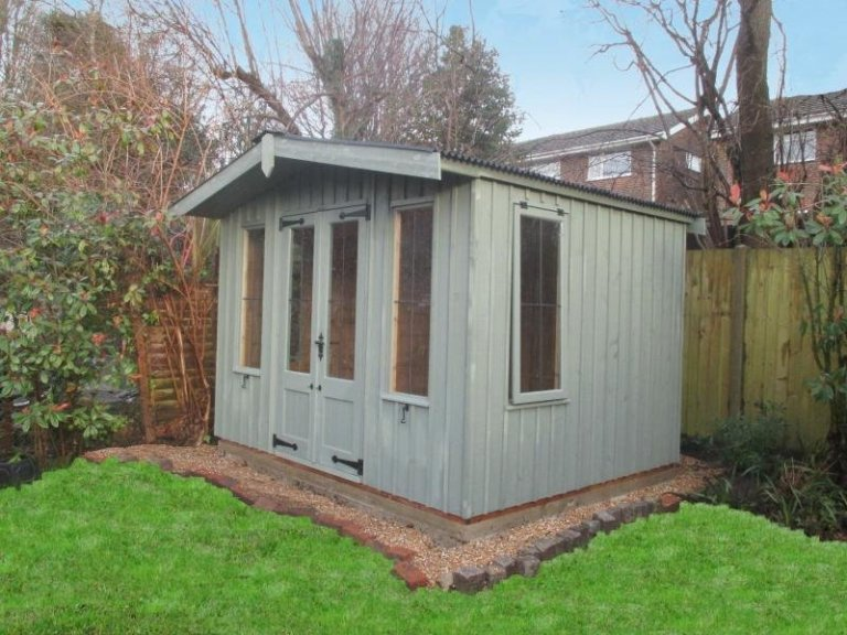 A traditional garden shed from the National Trust range of sheds and summerhouses, the Ickworth is a charming model with double doors and leaded windows. It has an apex roof with slight overhang and rustic timber cladding.