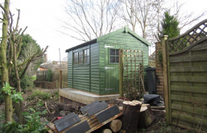 An attractive timber garden shed with apex roof covered in heavy-duty felt. It has georgian windows and is painted in Sikkens green preservative stain.