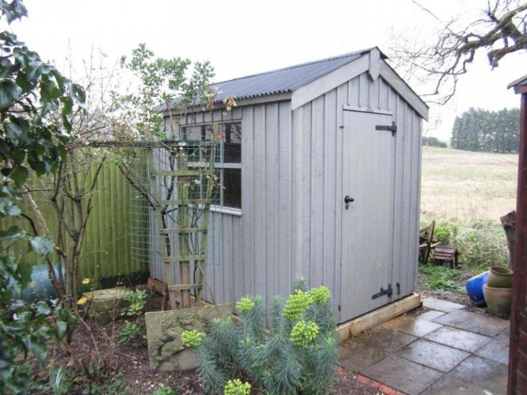 A national trust garden shed painted in the shade of wades lantern. The timber shed has vertical cladding, an apex roof and cast iron door furniture.