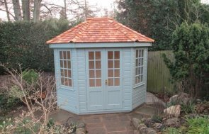 An attractive summerhouse with cedar shingle roof and shiplap exterior. It is painted in sage green paint and has georgian windows. The high quality timber summerhouse has insulation and pine lining.