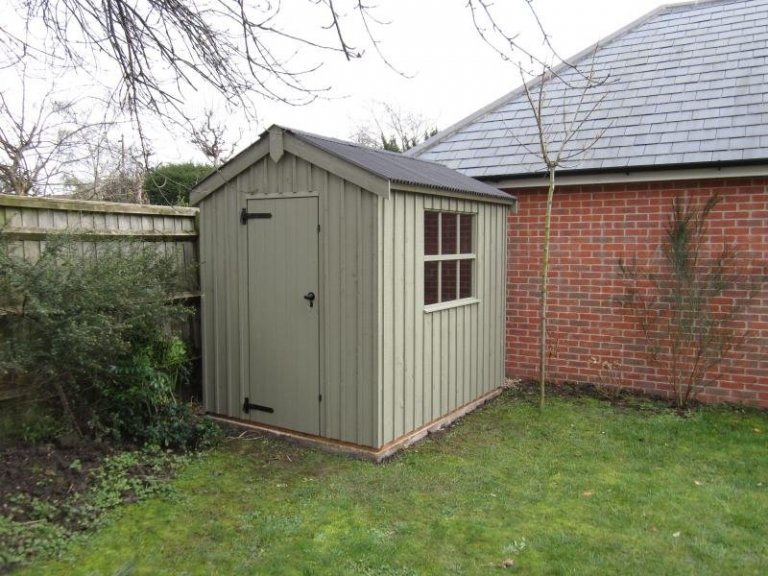 A traditional timber garden shed with corrugated roof and vertical cladding, From our range of National Trust sheds and summerhouses, the peckover shed is painted in our National Trust shade of disraeli green.