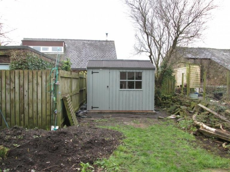 A traditional timber shed from our national trust range of sheds and summerhouses. The building has an apex corrugated roof and cast iron door furniture.