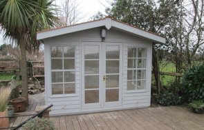 A stunning summerhouse with double doors and windows reminiscent of chalet-style beach huts. High quality timber summerhouse with roof overhang and insulated interior.