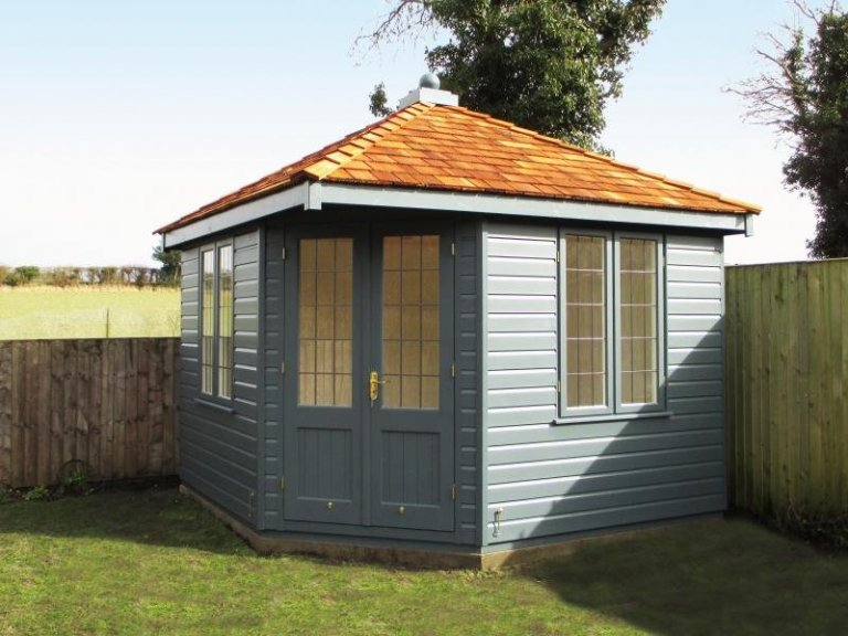 An attractive corner summerhouse with smooth shiplap cladding and a cedar shingle roof. The timber summerhouse has leaded windows and is painted in the external shade of Slate.