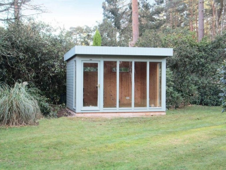 A modern and stylish garden studio set in beautiful surroundings with natural internal matchboard and a pent roof. The studio has several floor-to-ceiling windows and smooth shiplap cladding.