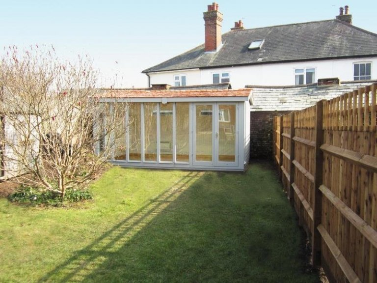 A modern garden studio with apex roof. A timber garden building with large windows and cedar shingle roof tiles.