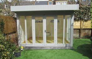A stylish and modern garden studio with painted interior. A timber garden studio with insulation and electrics along with a heater. The exterior has shiplap cladding and a pent roof.