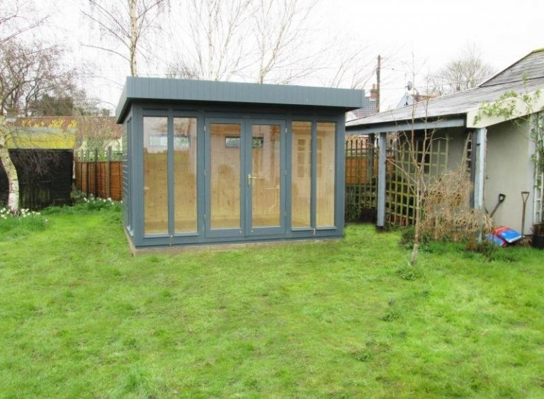 A stylish and contemporary wooden garden studio with insulation and pine lining. The salthouse studio is located in a grassy garden in a rural area and makes the perfect work from home office. The building is clad with smooth shiplap timber and painted in the exterior shade of slate.